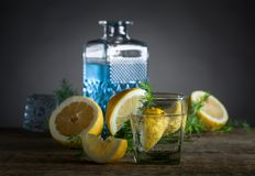 蓝色杜松子酒、补品和柠檬在一张老木桌上 图库摄影