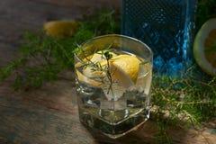 蓝色杜松子酒、补品和柠檬在一张老木桌上 库存照片