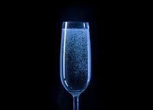 蓝色杯在黑背景的香槟 免版税库存照片