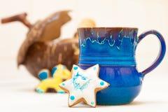 蓝色杯子和圣诞节姜饼结块星结冰装饰 图库摄影