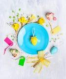 蓝色板材用黄色复活节彩蛋、假日装饰和黄水仙在木背景开花 库存图片
