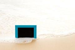 蓝色构筑了坐在沙子的黑板在海滩 免版税库存图片
