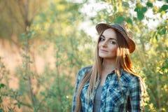 蓝色格子花呢上衣草帽的可爱的年轻白肤金发的妇女享受她的在掩藏的时间从太阳之外 库存图片