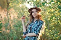 蓝色格子花呢上衣草帽的可爱的年轻白肤金发的妇女享受她的在掩藏的时间从太阳之外 免版税库存照片