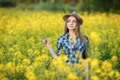 蓝色格子花呢上衣草帽的可爱的年轻白肤金发的妇女享受她的在明亮的五颜六色的开花的黄绿色草甸ha的时间 图库摄影