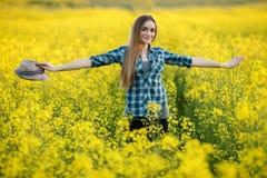 蓝色格子花呢上衣草帽的可爱的年轻白肤金发的妇女享受她的在明亮的五颜六色的开花的黄绿色草甸ha的时间 免版税库存照片