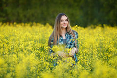 蓝色格子花呢上衣草帽的可爱的年轻白肤金发的妇女享受她的在明亮的五颜六色的开花的黄绿色草甸ha的时间 库存图片