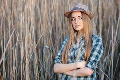 蓝色格子花呢上衣草帽的可爱的年轻白肤金发的妇女享受她的在狂放的灌木坚硬中午太阳的时间 免版税库存照片