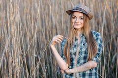 蓝色格子花呢上衣草帽的可爱的年轻白肤金发的妇女享受她的在狂放的灌木坚硬中午太阳的时间 免版税库存图片
