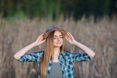 蓝色格子花呢上衣草帽的可爱的年轻白肤金发的妇女享受她的在草甸的时间户外 免版税库存照片