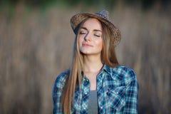 蓝色格子花呢上衣草帽的可爱的年轻白肤金发的妇女享受她的在草甸的时间户外 库存照片