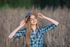蓝色格子花呢上衣草帽的可爱的年轻白肤金发的妇女享受她的在草甸的时间户外 库存图片