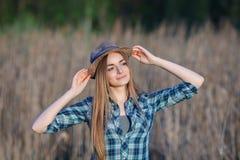 蓝色格子花呢上衣草帽的可爱的年轻白肤金发的妇女享受她的在草甸的时间户外 免版税库存图片