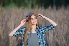 蓝色格子花呢上衣草帽的可爱的年轻白肤金发的妇女享受她的在草甸的时间户外 图库摄影