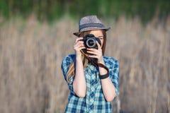 蓝色格子花呢上衣草帽的可爱的年轻白肤金发的妇女享受她的时间的拍在草甸的照片户外 图库摄影