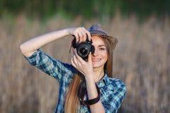 蓝色格子花呢上衣草帽的可爱的年轻白肤金发的妇女享受她的时间的拍在草甸的照片户外 库存照片