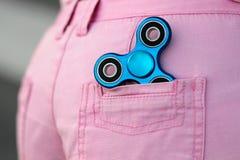 蓝色桃红色牛仔裤的后面口袋的金属普遍的坐立不安锭床工人短缺,忧虑安心玩具,反重音,并且放松坐立不安 图库摄影