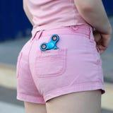 蓝色桃红色牛仔裤的后面口袋的金属普遍的坐立不安锭床工人短缺,忧虑安心玩具,反重音,并且放松坐立不安 库存照片