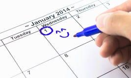 蓝色检查。盘旋在日历在2014年1月1日,新年 免版税库存图片