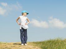 蓝色棒球帽的女孩站立在转动他的头的小山顶部 图库摄影