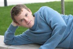 蓝色棕色毛发的轻的人斜倚的毛线衣 库存图片
