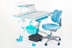 蓝色椅子、学校书桌、蓝色篮子、台灯和黑支持在腿下 库存图片
