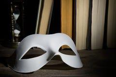 蓝色概念玻璃歌剧剧院天鹅绒 在书背景的白色古典狂欢节面具与在木桌上的葡萄酒滴漏 库存照片