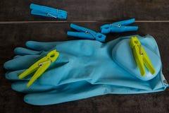 蓝色橡胶手套、肥皂和晒衣夹反对一黑暗的backgrou 库存照片