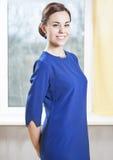 蓝色正式礼服的典雅和微笑的白种人深色的女性 库存图片