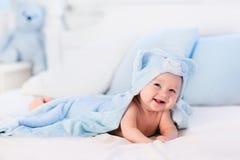 蓝色毛巾的男婴在白色床上 免版税图库摄影