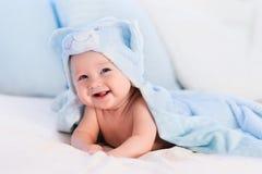 蓝色毛巾的男婴在白色床上 库存图片