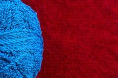 蓝色毛线丝球在红色背景的 免版税库存照片