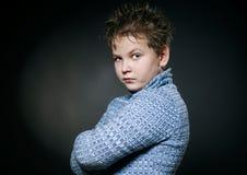 蓝色毛线衣的哀伤的男孩 库存图片