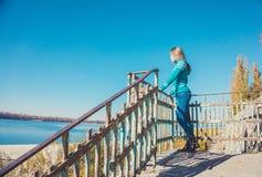 蓝色毛线衣的女孩反对清楚的蓝色秋天天空 免版税库存照片