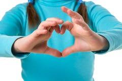 蓝色毛线衣的女孩用在心形关闭的手 免版税库存照片