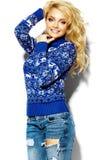 蓝色毛线衣的愉快的甜逗人喜爱的微笑的白肤金发的妇女 免版税库存照片