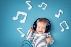 蓝色毯子背景的小男孩与耳机 库存照片