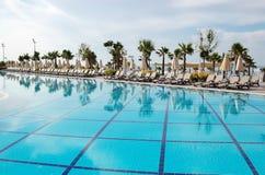 蓝色水池、伞和太阳床的看法在土耳其勒克斯 库存照片