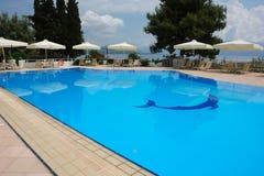 蓝色水池和白色伞的看法在现代化的希腊人旅馆里 免版税库存图片