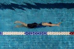 蓝色水池的少妇游泳者 免版税库存照片