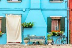 蓝色水色上色了有花、长凳和自行车的房子 五颜六色的房子在威尼斯,意大利附近的Burano海岛 威尼斯明信片 库存图片