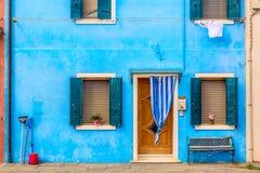 蓝色水色有花和长凳的色的房子 五颜六色的房子在威尼斯,意大利附近的Burano海岛 威尼斯明信片 著名地方 库存照片