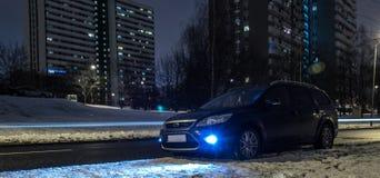 蓝色汽车在城市在晚上 免版税库存照片