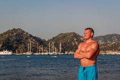 蓝色沐浴的短裤立场的被晒黑的白种人人在海滩在土耳其 库存图片
