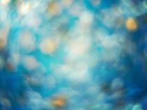 蓝色沙子抽象背景与闪闪发光的在焦点外面 免版税库存照片