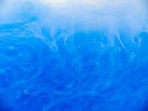 蓝色油漆在水中,关闭看法 抽象背景 蓝墨水下落被溶化入液体 丙烯酸酯云彩打旋 免版税图库摄影
