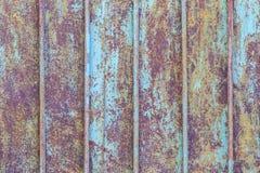 蓝色油漆绘的老金属篱芭的片段作为背景 免版税库存照片