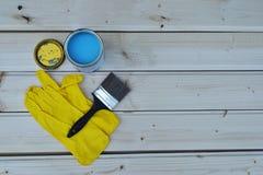 蓝色油漆罐头、刷子和黄色手套 库存照片
