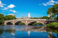 蓝色波士顿桥梁校园查尔斯时钟哈佛约翰在河天空塔结构树大学w星期 几星期跨接与在查尔斯河的钟楼 免版税库存照片