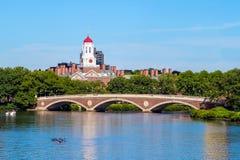 蓝色波士顿桥梁校园查尔斯时钟哈佛约翰在河天空塔结构树大学w星期 几星期跨接与在查尔斯河的钟楼 免版税库存图片